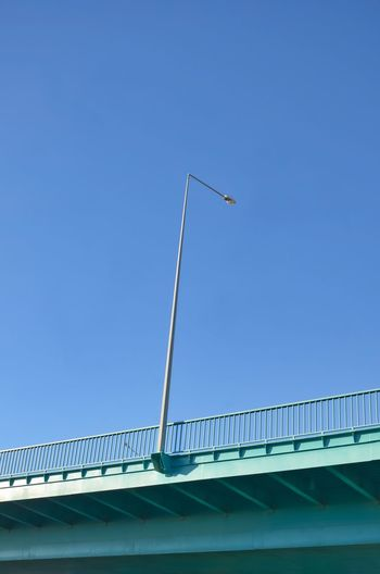 streetlight on a bridge with blue sky Bridge Street Light Lightning Equipment Sky Low Angle View Clear Sky Blue Day No People Copy Space Bridge - Man Made Structure Outdoors Railing