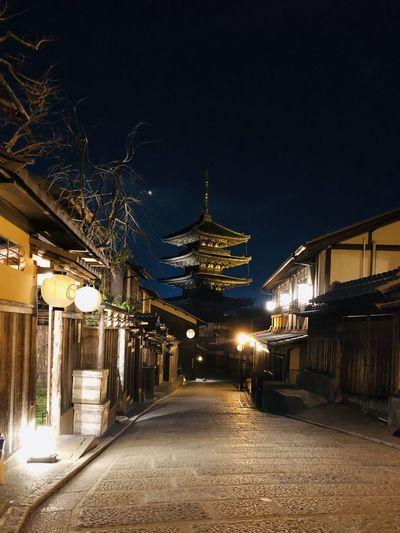 Illuminated bridge amidst buildings against sky at night