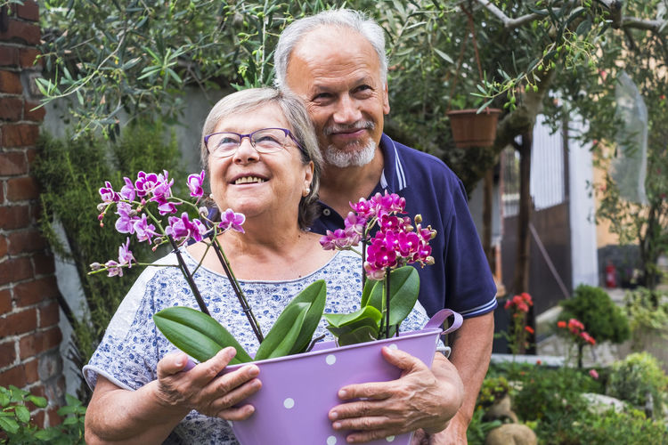 Smiling couple with potted plants standing at yard