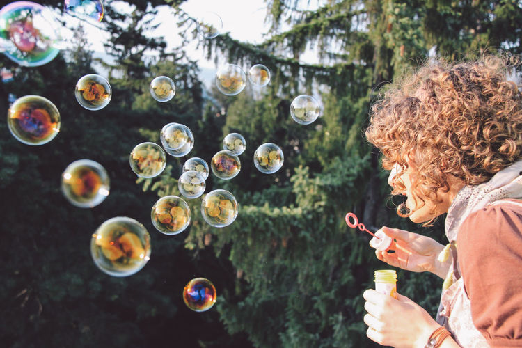 Woman Blowing Bubbles From Wand
