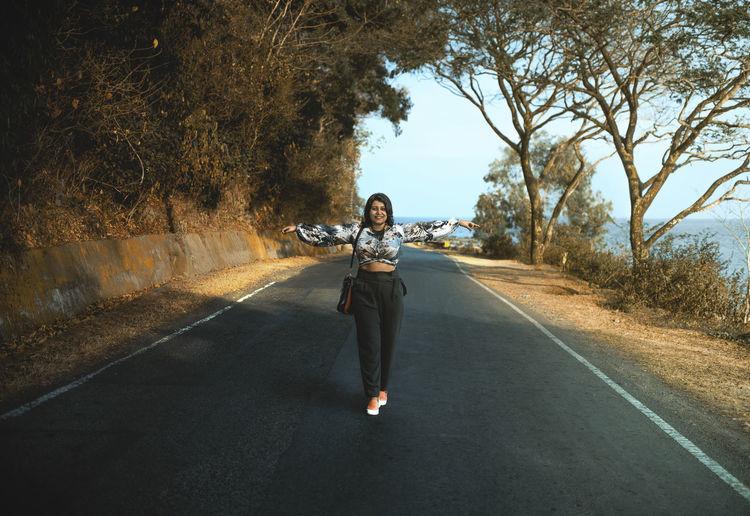 Full length portrait of woman on road