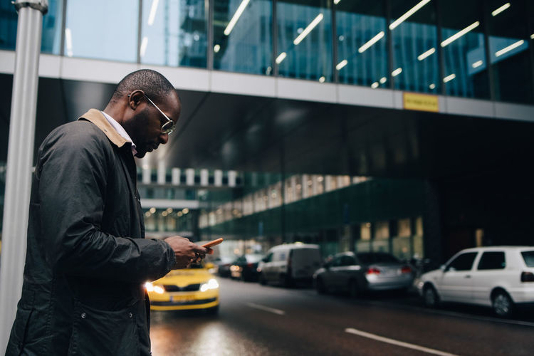 Side view of young man holding smart phone in city