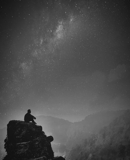 Silhouette man sitting on rock against star field