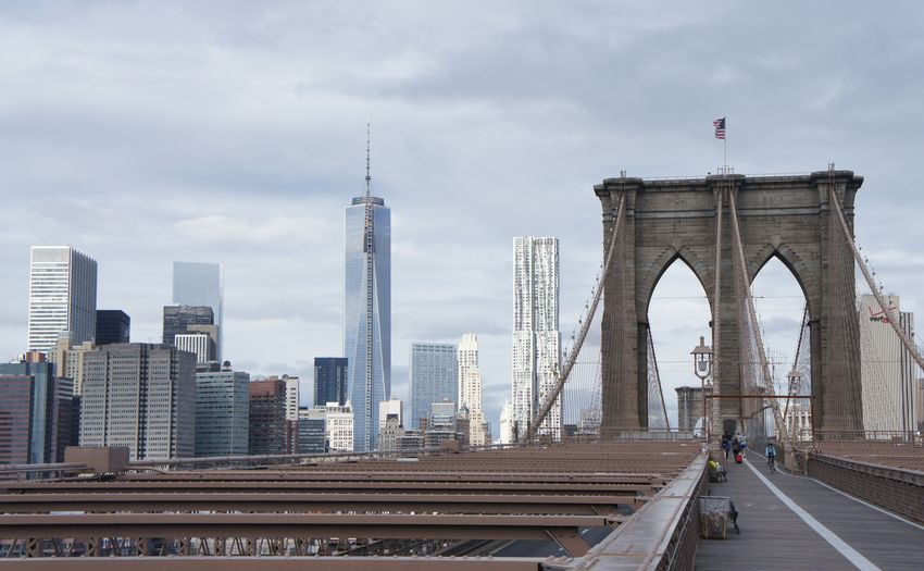 View of bridge in city against cloudy sky
