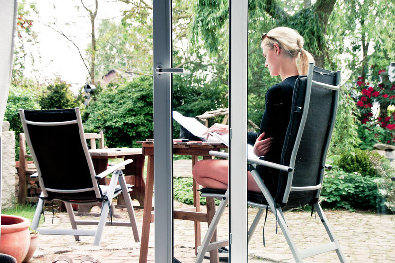 Young Woman Reading Book While Sitting On Chair Seen Through Glass Door