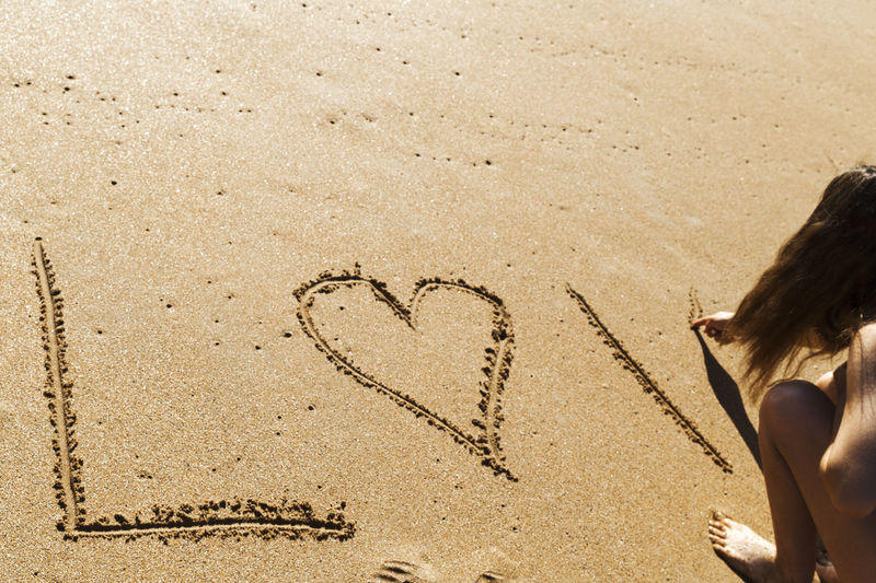 Young woman writing the word love in the sand of a beautiful beach