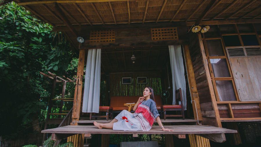 Full length of woman looking away while sitting on wooden plank against house