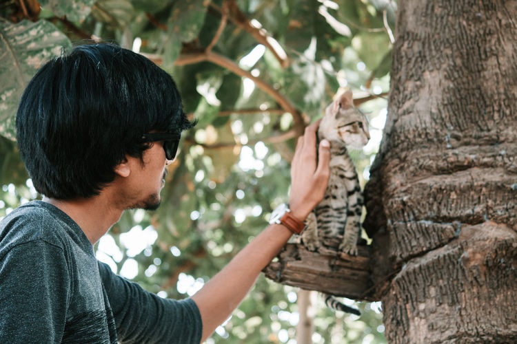 One Animal Tree One Person Mammal Tree Trunk Young Adult Trunk Young Men Headshot Vertebrate Day Side View Casual Clothing Nature Real People Leisure Activity Portrait Outdoors Zoo Cat Kitten