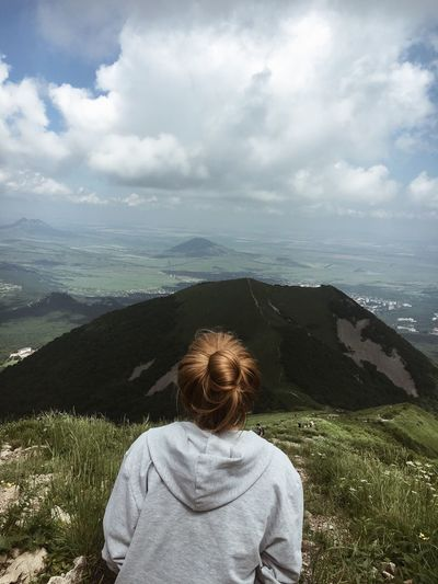Rear view of woman on mountain against cloudy sky