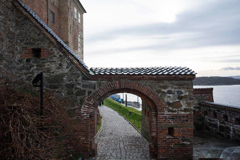 Arch bridge over building against sky