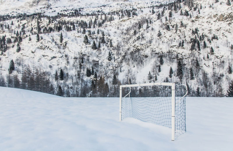 Soccer goal on snow covered land during winter