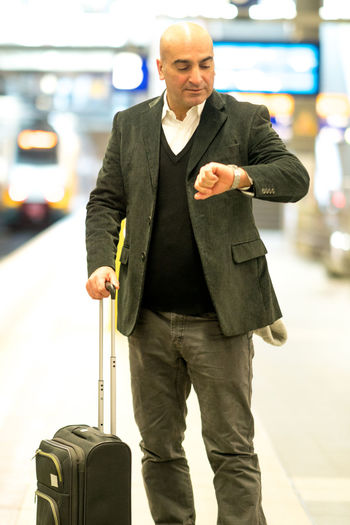 Mature Man With Suitcase Checking Time At Railroad Station Platform