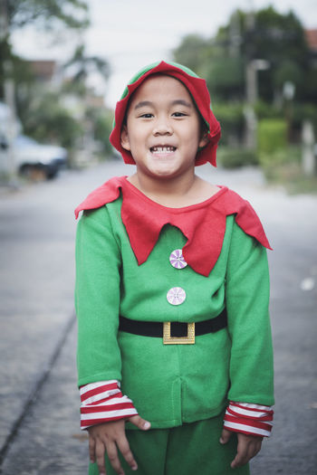 Portrait of smiling boy in costume standing outdoors