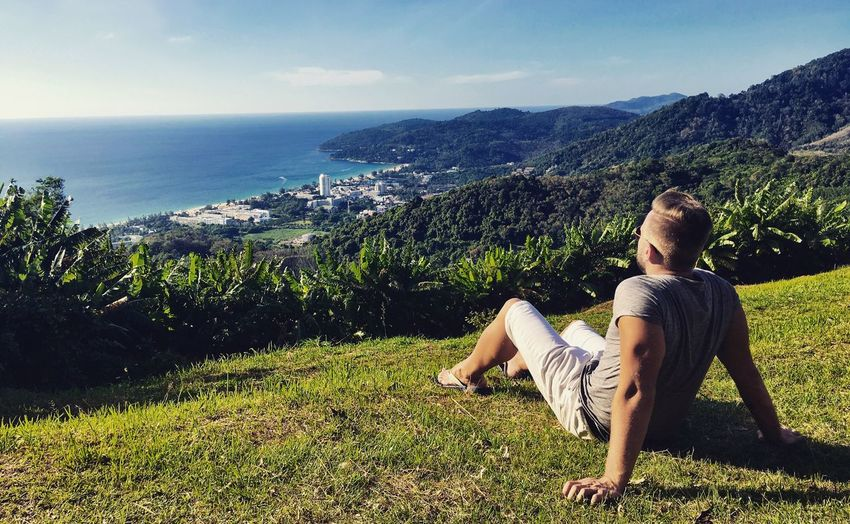 Young Man Sitting On Grassy Mountain Against Sea