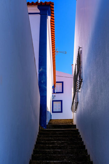 Low angle view of staircase amidst buildings against blue sky