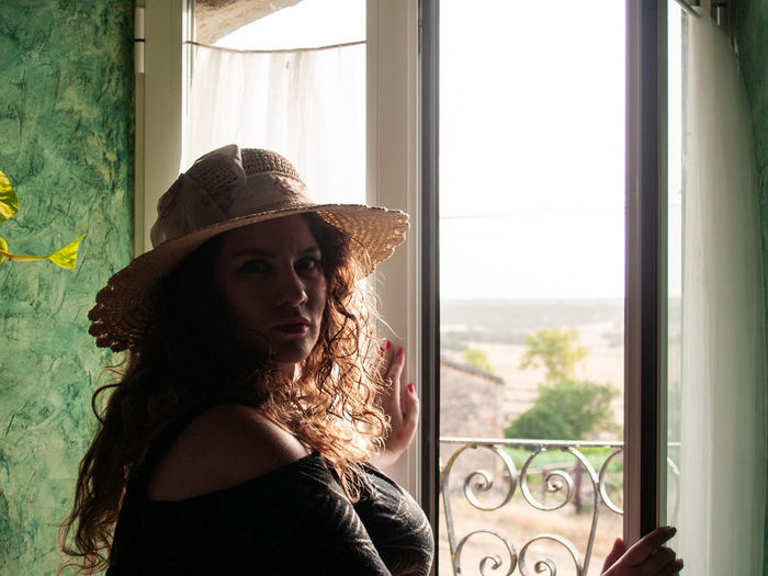 Portrait Of Woman Wearing Hat While Standing Against Window At Home