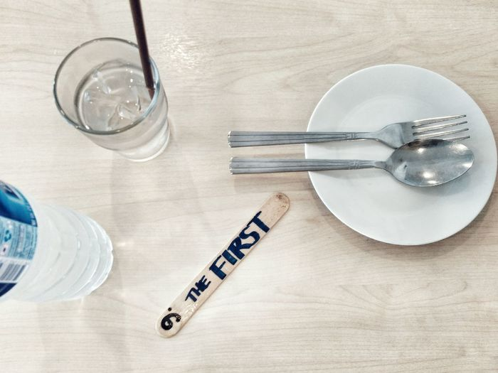 High angle view of drink by cutlery with text on stick at table