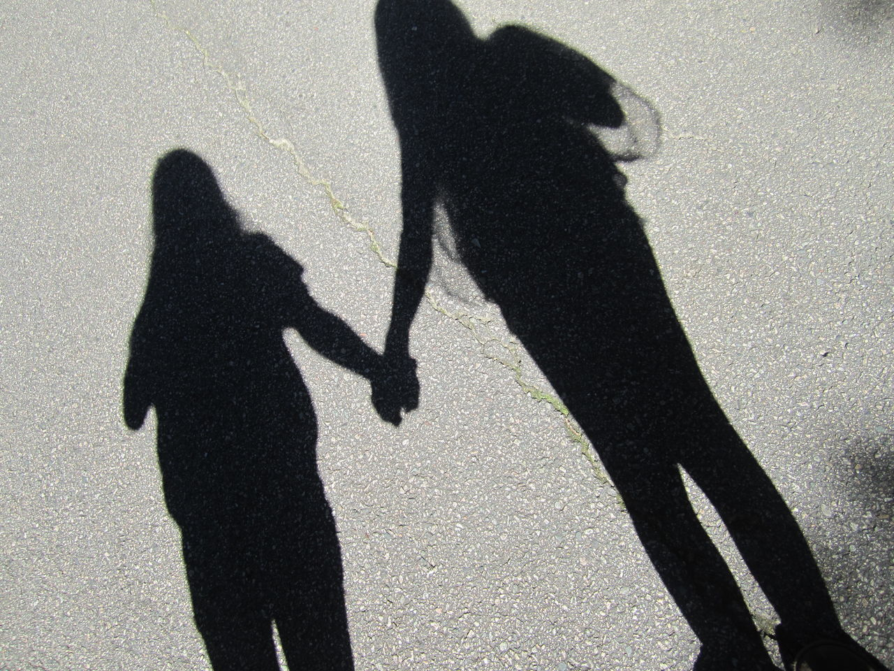 Shadow Of Female Friends Standing On Street