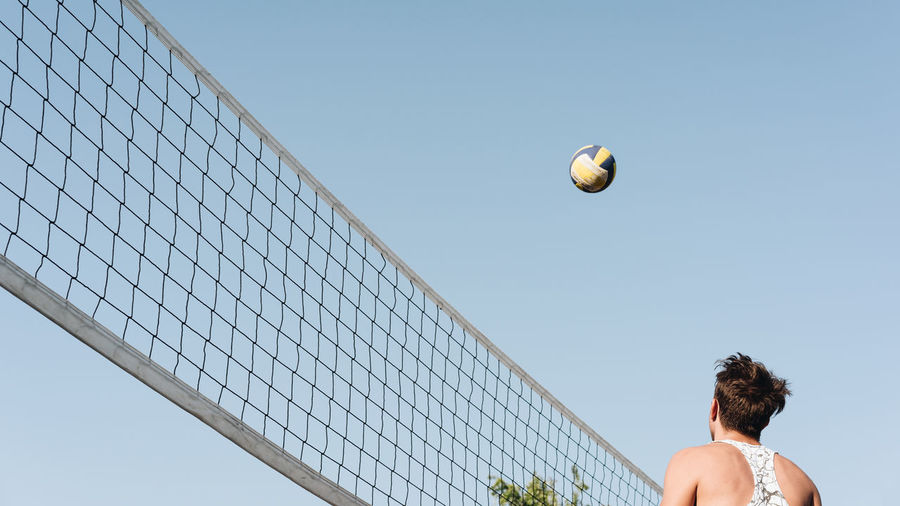 Low angle view of man playing volleyball against clear sky