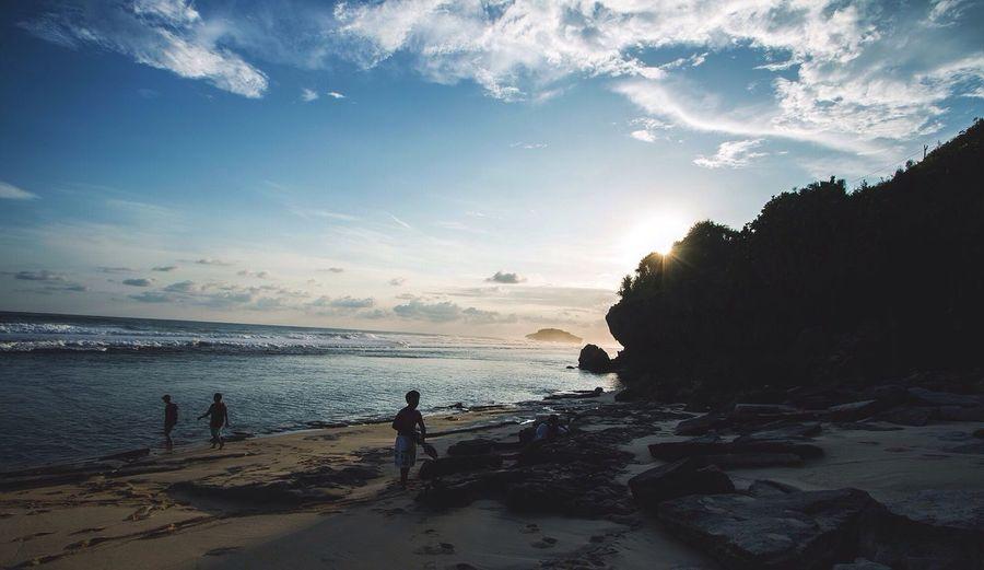 People walking along sandy beach at sunset