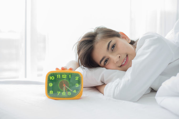 Portrait Of Smiling Young Woman With Alarm Clock Lying On Bed At Home