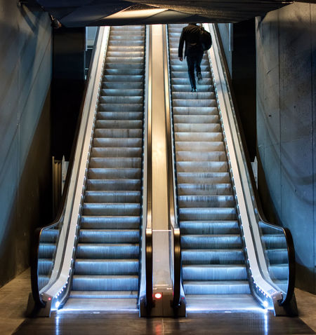 Man ascending an escalator from a subway riding up the moving treads towards daylight at the top, view from the bottom Ascending Rear View Steps Top Tread Underground Architecture Climbing Double Escalator Exit Indoors  Level Lifestyles Men Modern Moving Up One Person Staircase Steps Steps And Staircases Subway Up Upward View