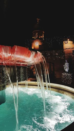 Illuminated fountain in swimming pool at night