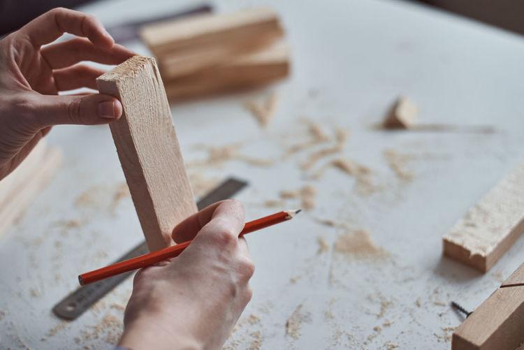 Cropped hands of carpenter holding wood at workshop