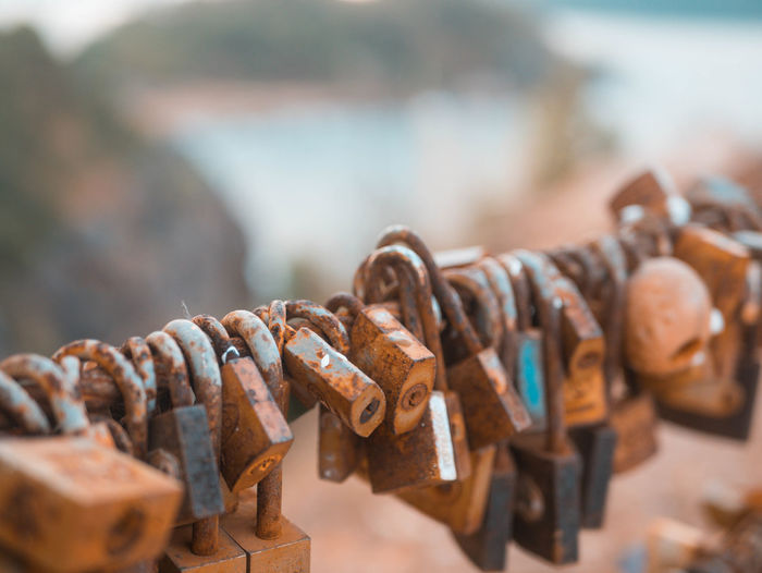 Close-up of padlocks hanging on rusty metal