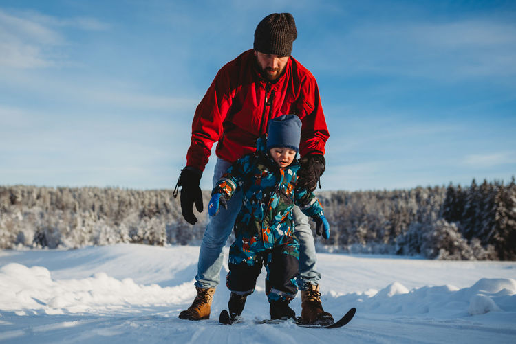 Full length of father with son on snow
