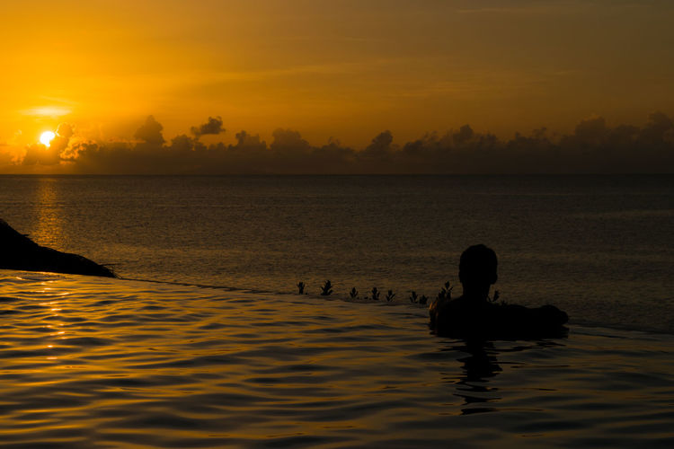 Silhouette man swimming in infinity pool by sea against sunset sky