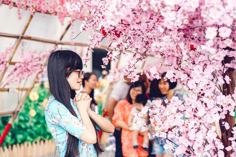 Young woman with pink flowers on tree