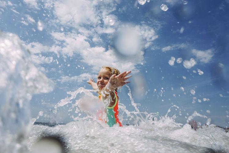 Full length of girl splashing water