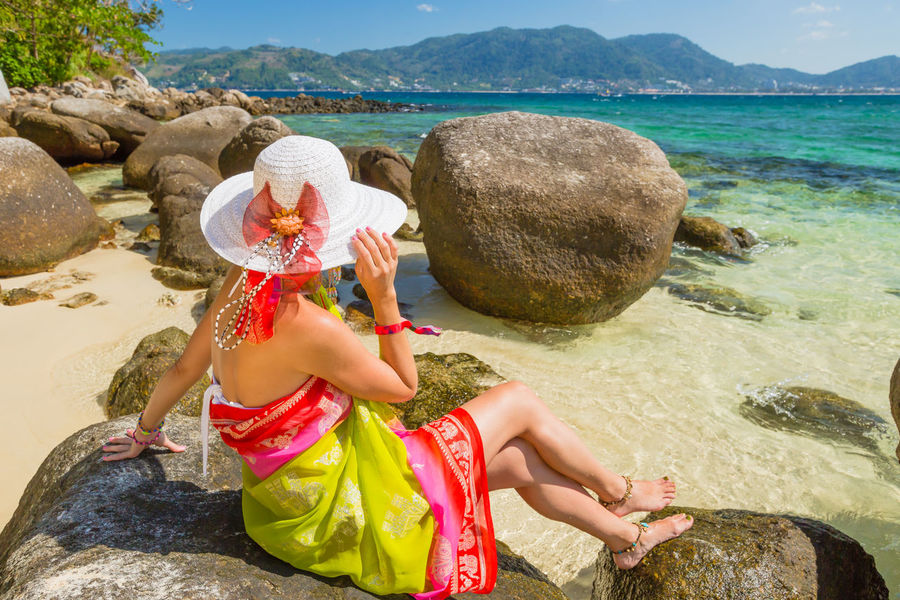 Back of happy and fashionable tourist woman with colorful sarong in turquoise water of Maya Bay famous lagoon of The Beach movie, Phi Phi Leh, Andaman Sea in Thailand Fashionable and happy tourist with sarong and pink wide-brimmed hat making a selfie on tropical famous beach of Nai Harn Beach, Rawai, Phuket, Thailand. Happy tourist enjoys panorama from Sail Rock View Point of kor 8 of Similan Islands National Park, Phang Nga, Thailand, one of the tourist attraction of the Andaman Sea. Happy woman with bikini and shorts, jumping in the air on Ya Nui Beach, a little cove divided by a rocky cape, Phuket, Thailand, Asia. Happy Koh Rok Islands Nui Beach Phang Nga Bay Phuket Thailand Tanning ☀ Thailand Vacations Woman Adult Beach Beautiful Woman Beauty Beauty In Nature Day Full Length Girl Koh Rok Lifestyles Nature One Person Outdoors People Phang Nga Portrait Rawai Real People Rock - Object Sea Seascape Sitting Surin Islands Travel Destinations Tree Water Women Young Adult Young Women