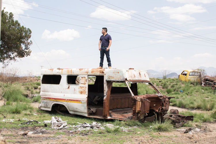 Man standing on abandoned car on field against sky