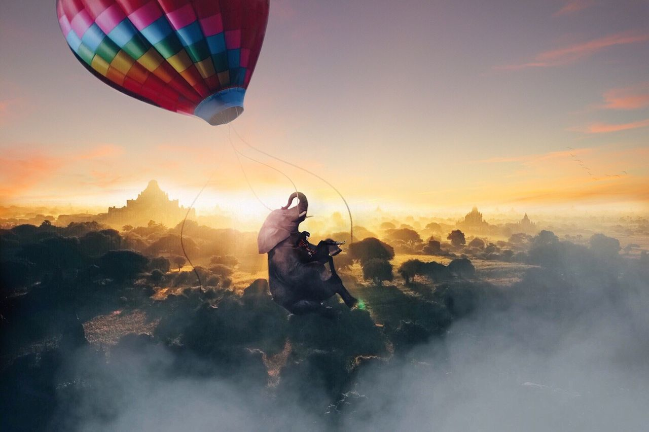 hot air balloon, mid-air, sunset, sky, adventure, fog, flying, nature, outdoors, parachute, air vehicle, cloud - sky, transportation, real people, men, togetherness, landscape, scenics, beauty in nature, ballooning festival, mountain, dawn, extreme sports, building exterior, day, paragliding