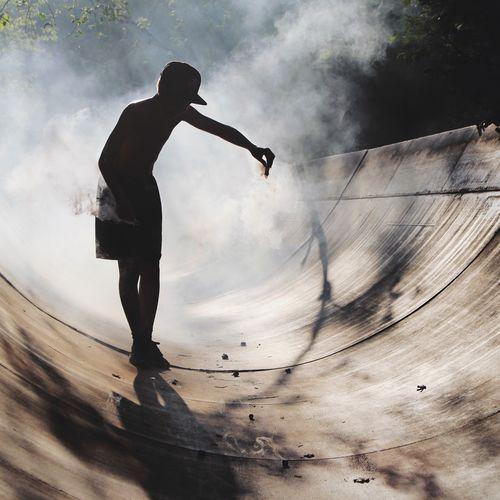 Full length of boy spreading smoke at skateboard park