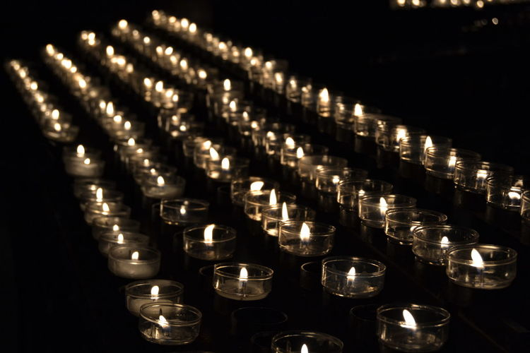 Row Of Illuminated Candles In Church