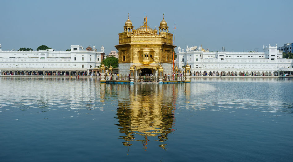 Reflection of golden temple in lake against clear sky