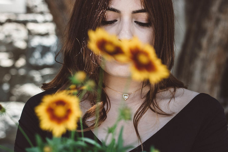 Young beautiful woman behind yellow flowers