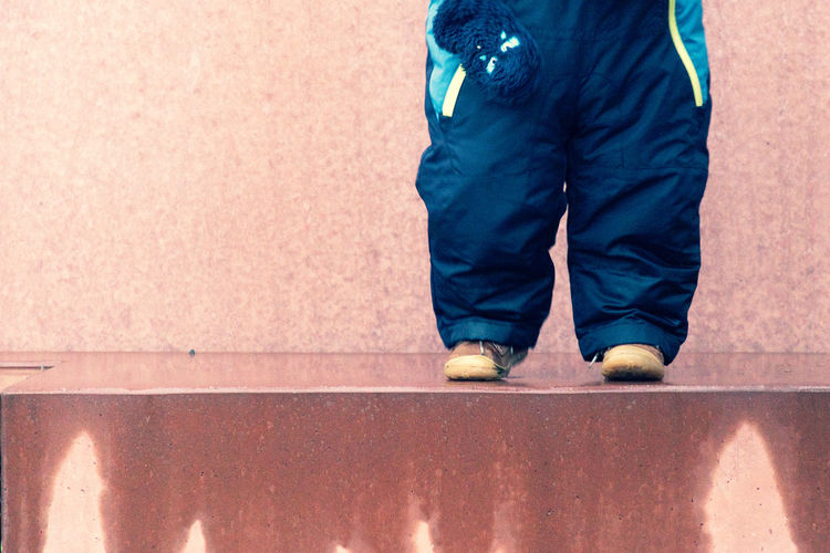 Low Section Of Child Standing On Wet Floor Against Wall