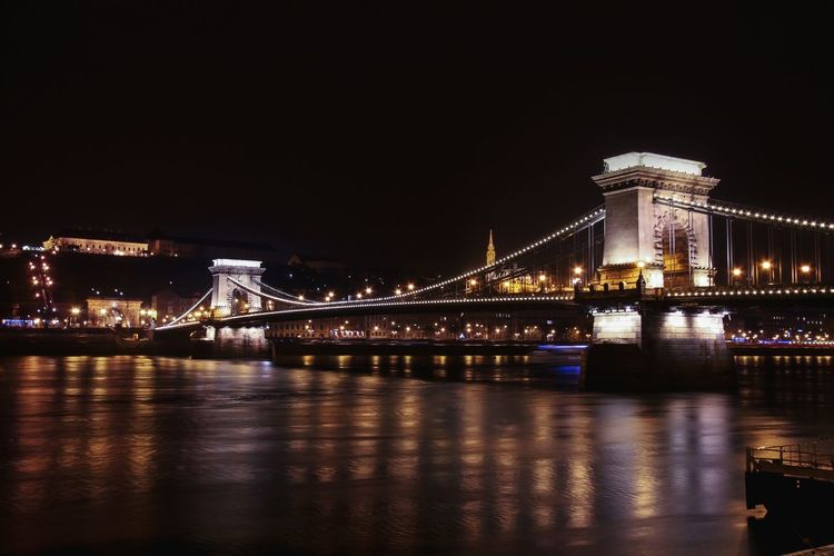 Chain bridge over danube river with light reflection at night