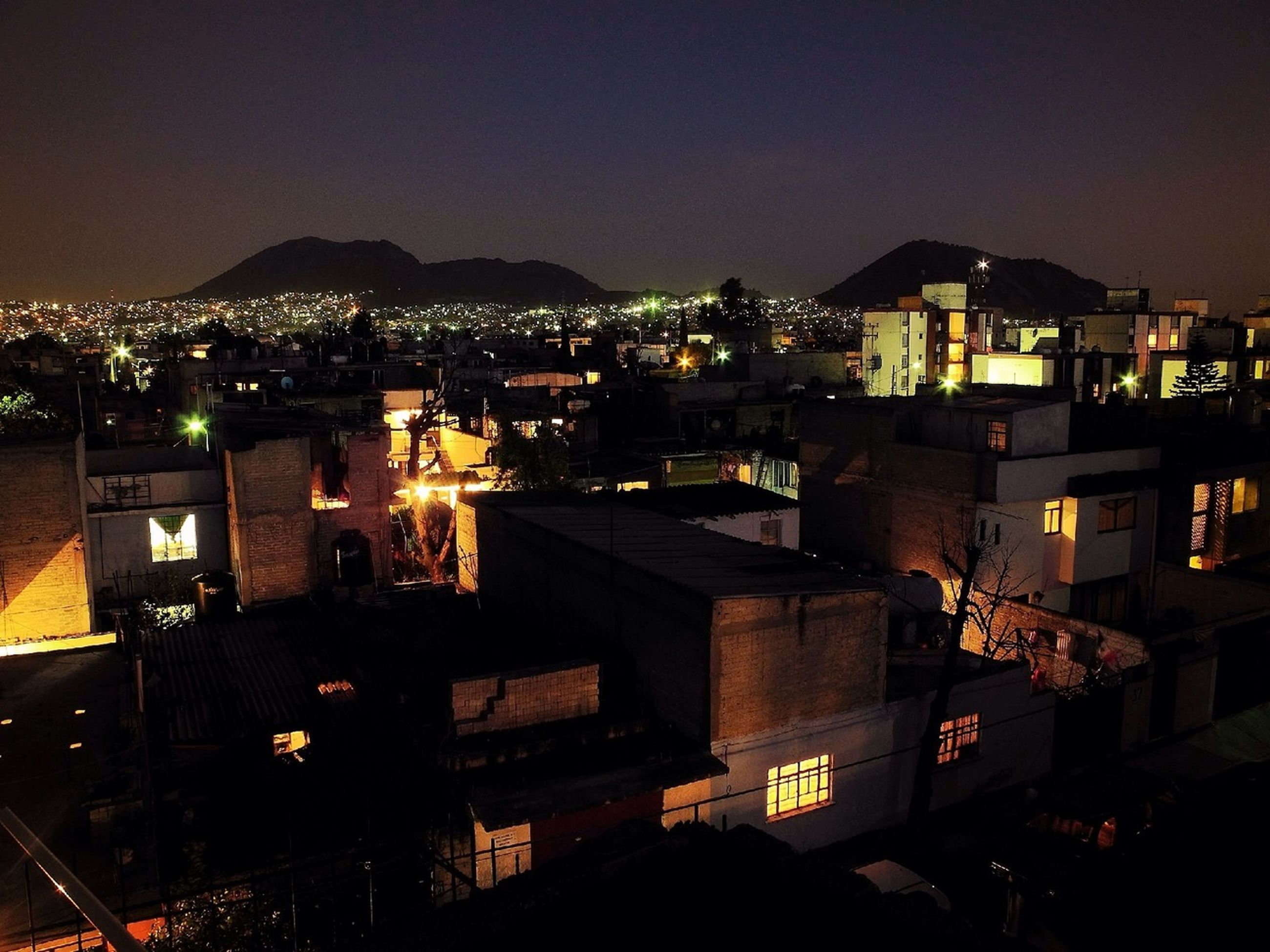 illuminated, night, building exterior, built structure, architecture, city, high angle view, residential building, cityscape, residential structure, house, dark, residential district, copy space, sky, clear sky, mountain, town, lighting equipment, outdoors