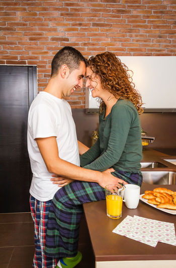 Portrait of loving young couple looking at each other while having breakfast on the home kitchen Fresh Thirties Relaxing 30s Coffee Orange Juice Drink Food Morning Husband Family Wife Portrait People Indoors  House Lovers Cheerful Girl Boyfriend Handsome Happiness Affection Two Adult Girlfriend Smiling Attractive Romance Lifestyle Female Young Caucasian Male Together Relationship Other Each Looking Breakfast Kitchen Home Man Woman Happy Embracing Couple Romantic Love