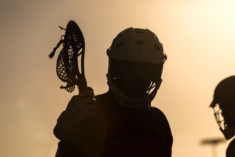 Silhouette Lacrosse Players Against Sky During Sunset