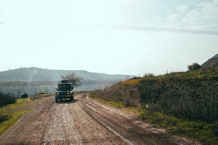Car on dirt road amidst field against sky