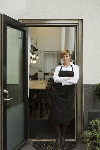 Portrait of woman standing against door