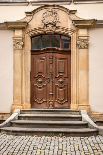 Old door of a historical building with coats of arms made of stone Architecture Entrance Door Building Exterior Built Structure Closed Building Day Staircase No People History The Past Front Door Wood - Material Craft City Carving - Craft Product Residential District Doorway House Outdoors Wood Ornate Bas Relief