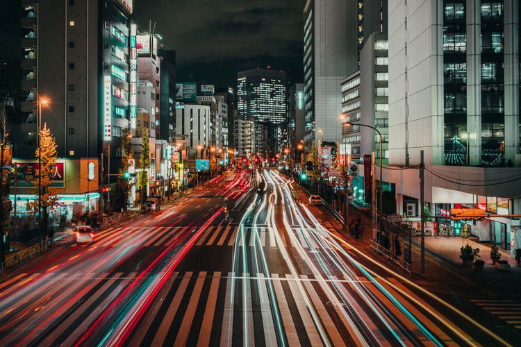 Light trails on road along buildings at night