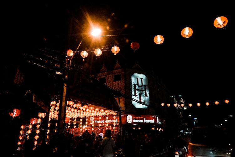 People on illuminated street against sky at night
